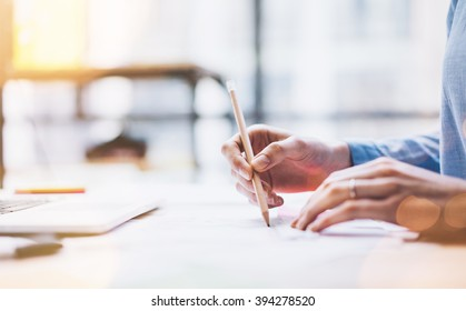 Photo young architect work concept. Woman working with new startup project in modern loft. Drawning pencil. Notebook on wood table. Horizontal, film effect
