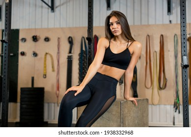 Photo of a young athlete in black clothes who sits on a wooden box in the gym after performing exercises. High quality photo