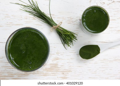 Photo of young barley powder and drink with grass bunch on white wooden surface; concept of superfood