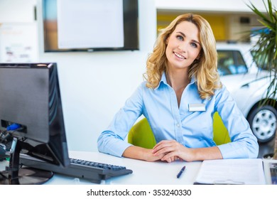 Photo of young beautiful business woman in car showroom. Young business woman working with computer and looking at camera. Modern office interior