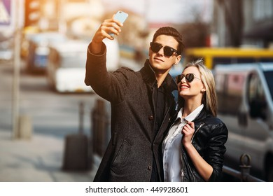 Photo of a young beautiful couple making selfie on a busy city street
