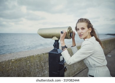 photo of young beautiful girl looking in telescope