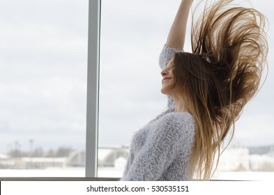 Photo of young beautiful happy smiling woman with long hair near the window. Girl looking at the camera. Female fashion. Sunny day. City lifestyle. Waist up. Toned