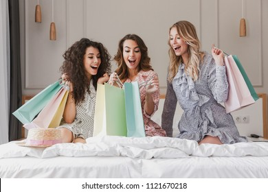 Photo of young beautiful women 20s wearing dresses unpackaging colorful shopping bags while resting on luxury bed in hotel room during bachelorette party