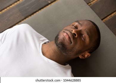 Photo of young black man lying in Dead Body exercise or Corpse pose with his eyes closed, Savasana pose, working out, resting after practice, close up, studio, top view. Healthy lifestyle concept