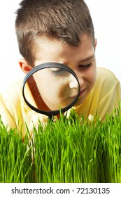 Photo of young boy looking at green grass through magnifying glass