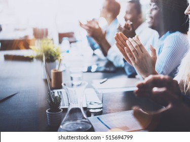 Photo of young business partners applauding to reporter after listening report at seminar. Professional education, work meeting, presentation or coaching concept.Horizontal,blurred background