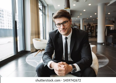 Photo of young businessman wearing formal black suit and eyeglasses sitiing on armchair in hotel lobby