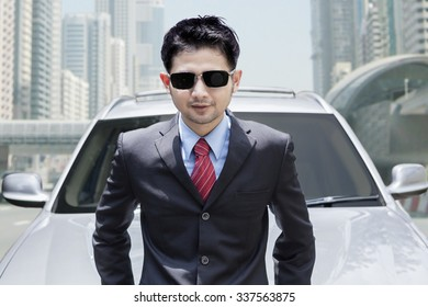 Photo of young businessman wearing formal suit and sunglasses in front of new car