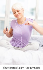 photo of young caucasian woman sitting on a bed and shaking while listening music with headphones