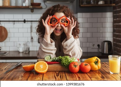 Photo of young caucasian woman smiling while cooking salad with fresh vegetables in kitchen interior at home