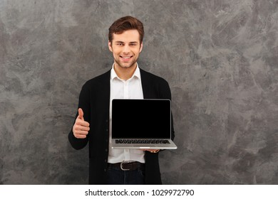 Photo of young cheerful businessman standing over grey wall background. Looking camera showing display of laptop computer make thumbs up.