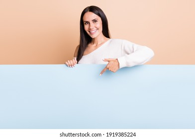 Photo of young cheerful girl happy smile point finger empty space poster ad promo offer isolated over beige color background