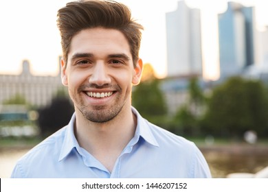 Photo of a young cheerful happy smiling businessman standing outdoors on the street with beautiful sunlight over lake background.