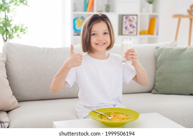 Photo of young cheerful little girl happy positive smile drink milk eat cornflakes breakfast show thumb-up like recommend choice home