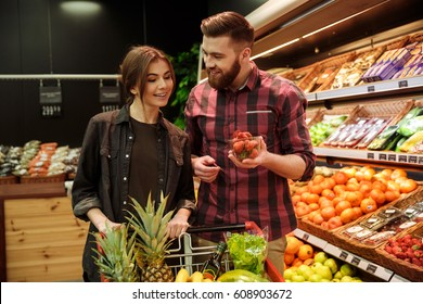 Photo of young cheerful loving couple in supermarket with shopping trolley choosing fruits. Looking aside.