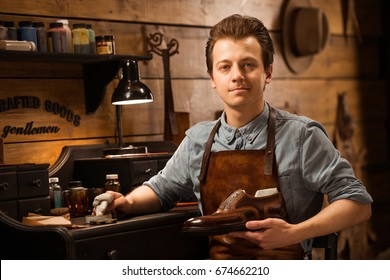 Photo of young cheerful shoemaker in workshop holding shoes. Looking at camera.
