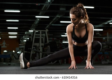 Photo of young concentrated strong fitness lady make sport stretching exercise in gym. Looking aside.