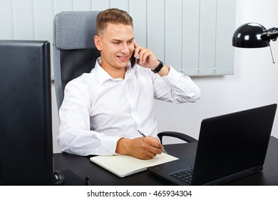 Photo of a young confident businessman talking on the mobile phone