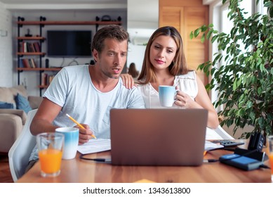 Photo of young  couple calculating their  bills at home.
