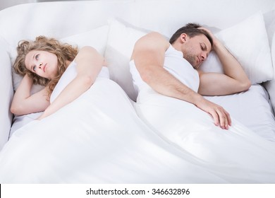 Photo of young couple in crisis lying in bed
