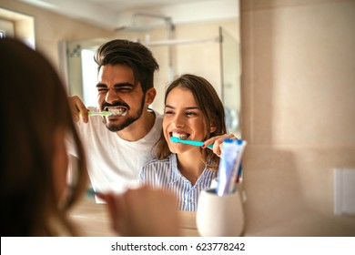 Photo of young couple having fun while brushing teeth in the bathroom.