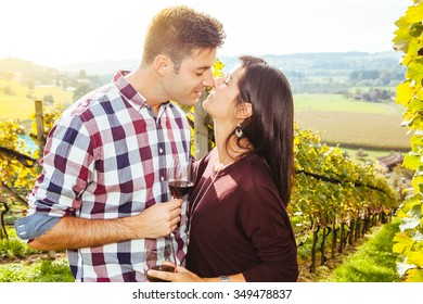 Photo of a young couple kissing and drinking wine in a vineyard.