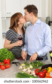 Photo of a young couple kissing in their kitchen while preparing food and drinking wine.