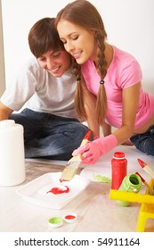 Photo of young couple mixing paints while sitting on floor in new flat