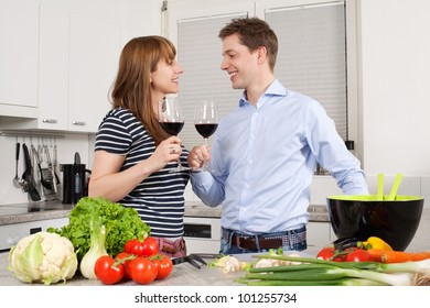Photo of a young couple preparing salad in their kitchen and drinking wine.