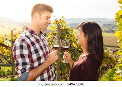 Photo of a young couple tasting and drinking wine in a vineyard.