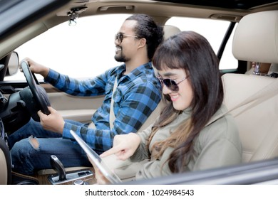 Photo of young couple using a digital tablet while enjoying road trip, isolated on white background