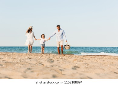 Photo of young cute happy family having fun together at the beach.