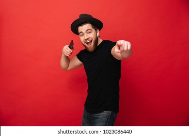 Photo of young delighted man wearing black t-shirt and hat singing while listening to music on cell phone and wireless earphones isolated over red wall