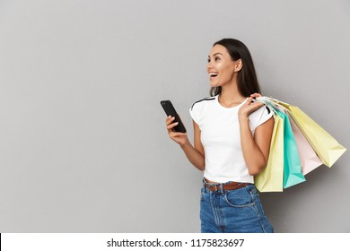 Photo of young excited cheerful woman holding shopping bags isolated over grey background using mobile phone looking aside.