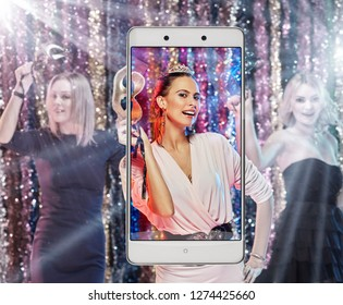 Photo of young excited woman dancing on xmas party, smart device concept