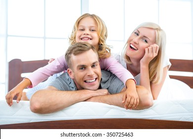 Photo of young family of three lying on nice white bed. Young family demonstrating quality of mattress