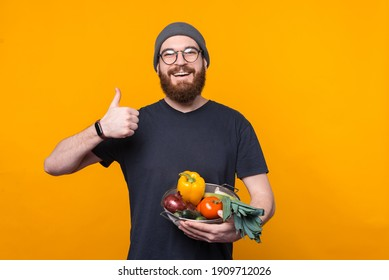 Photo of young farmer showing thumb up and holding fresh raw vegetables.