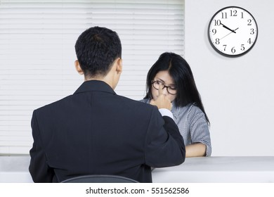 Photo of a young female worker looks scared while scolding by her boss in the office