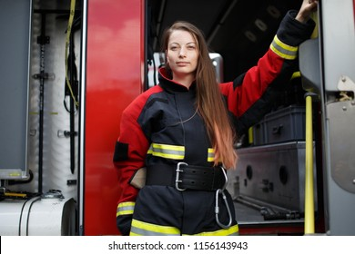 Photo of young fire woman with long hair in overalls looks at camera next to fire engine