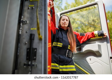 Photo of young fire woman with long hair in overalls stands in fire engine