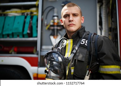 Photo of young firefighter standing near fire truck with fire hose