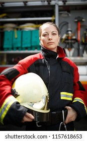 Photo of young firefighter woman staring into camera next to fire engine