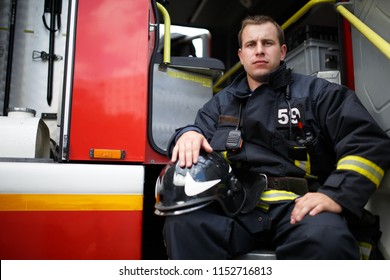 Photo of young fireman looking at camera in fire truck