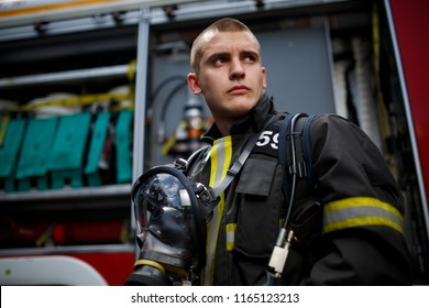 Photo of young fireman near fire engine