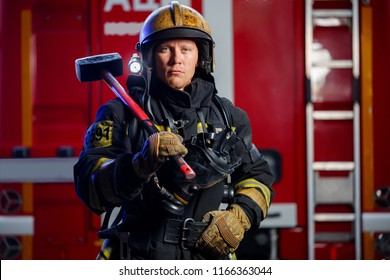 Photo of young fireman with sledgehammer in hands near fire engine