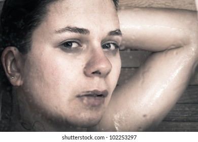 Photo of young frightened woman through wet glass of shower.