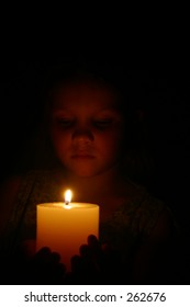 Photo of a young girl holding a candle.