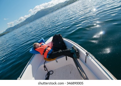 Photo of the young girl lying on a prow of a boat