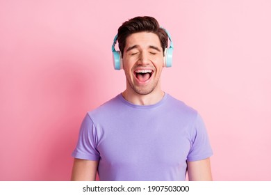 Photo of young handsome man happy positive listen music earphones sing isolated over pink color background